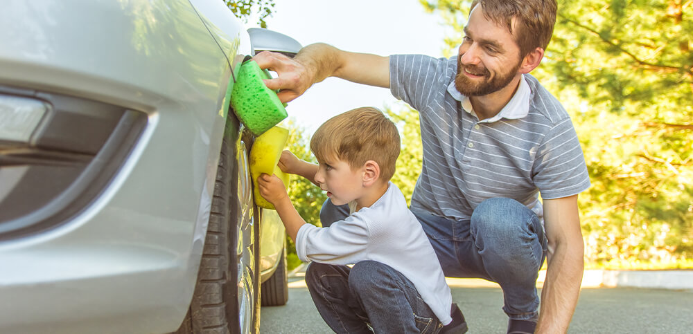 toddler and dad cleaning car.